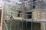 Parapet stone wall with brick quoin corners